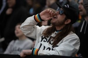 Long-haired, beared person wearing sunglasses calls out with the crowd behind