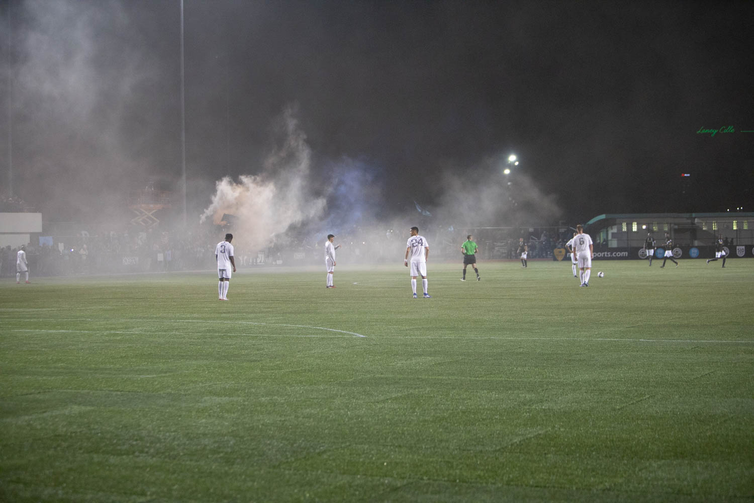 Smoke hovers over the soccer field