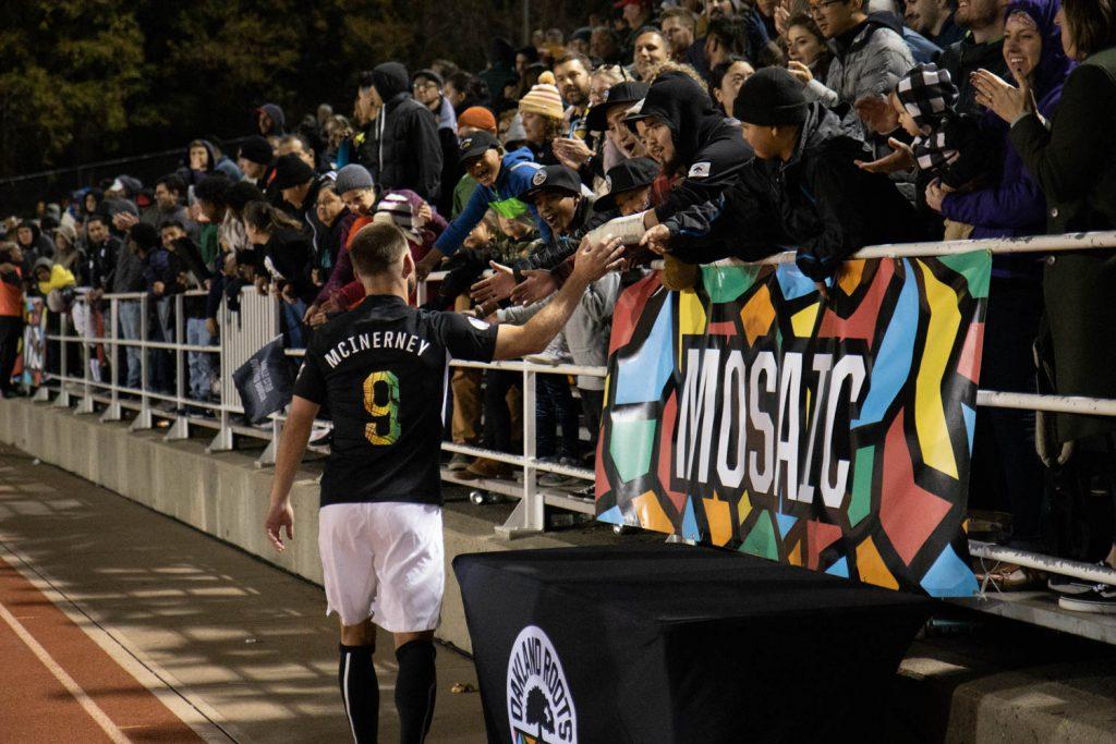 Soccer player high-fives fans leaning over bleachers
